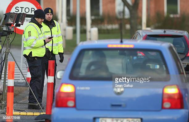 Danish police conducting spot checks on incoming traffic from Germany watch cars arriving on a country road on January 6 2016 near Padborg Denmark...