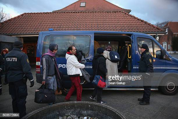 Danish police escort a family from Syria seeking asylum in Denmark after finding them while checking the identity papers of passengers on a train...