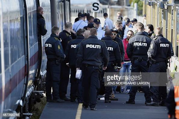 Danish police guards a train with migrants mainly from Syria and Iraq at Rodby railway station southern Denmark on September 9 2015 The migrants...