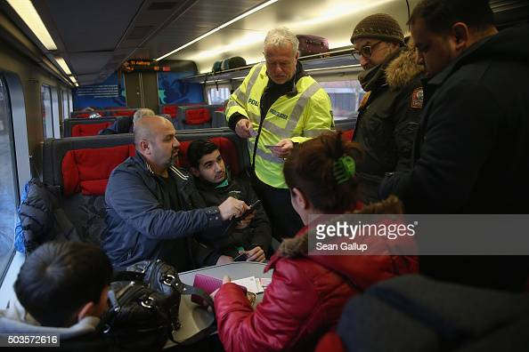 Danish policeman checks the identity papers of passengers on a train arriving from Germany on January 6 2016 in Padborg Denmark Denmark introduced a...