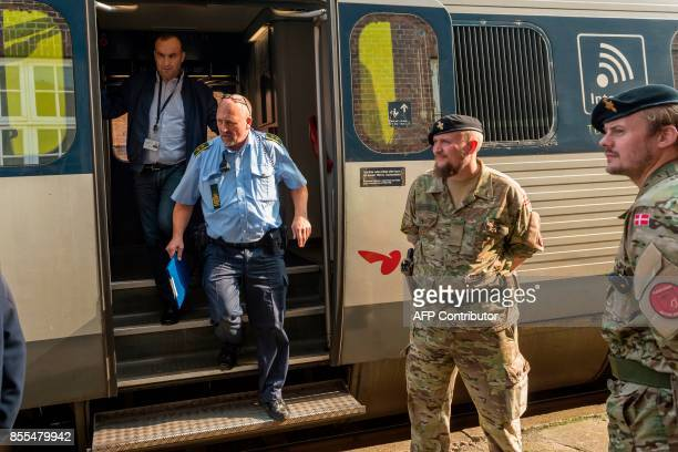 A Danish policeman exits a train as Danish soldiers look on at the DanishGerman border train station in Padborg on September 29 2017 Armed forces...