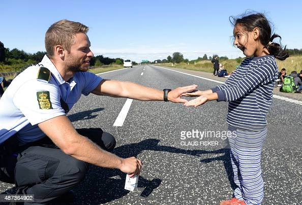 Danish policeman plays with a migrant girl as a group of migrants attempt to walk at the E45 freeway from Padborg on the DanishGerman border towards...