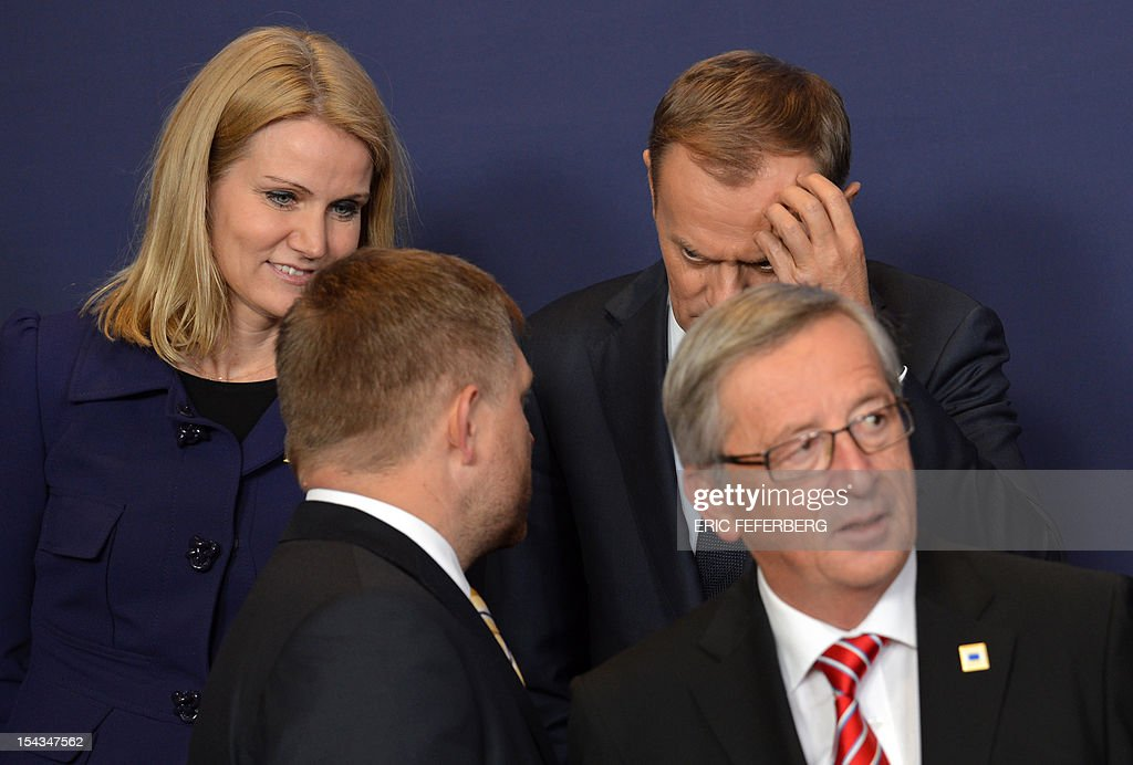 Danish Prime Minister Helle Thorning-Schmidt (top L) and Polish Prime Minister Donald Tusk (top R) talk with Slovak Prime Minister Robert Fico (bottom L) as they take their positions for a family photo during an EU summit in Brussels on October 18, 2012. EU leaders today go into the first of three summits before Christmas on strengthening the bloc's foundations, with France saying an end to the crippling eurozone debt crisis is 'very close.' FEFERBERG