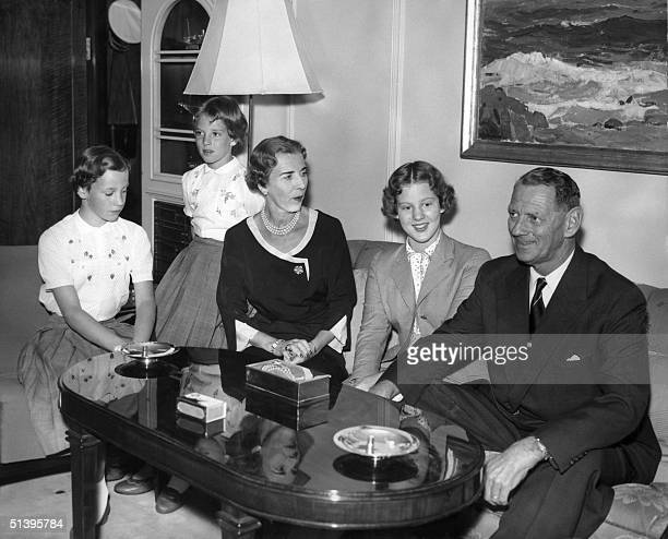 Danish Queen Ingrid and her husband King Frederik IX are surrounded 01 August 1956 around a table in the lounge of the Danish Royal yacht harboured...