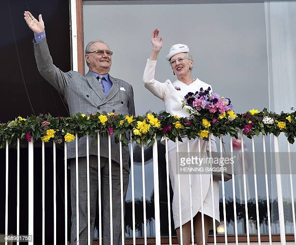 Danish Queen Margrethe and Prince Consort Henrik wave to the attendees from the balcony at Aarhus City Hall on April 8 as a prelude to the...