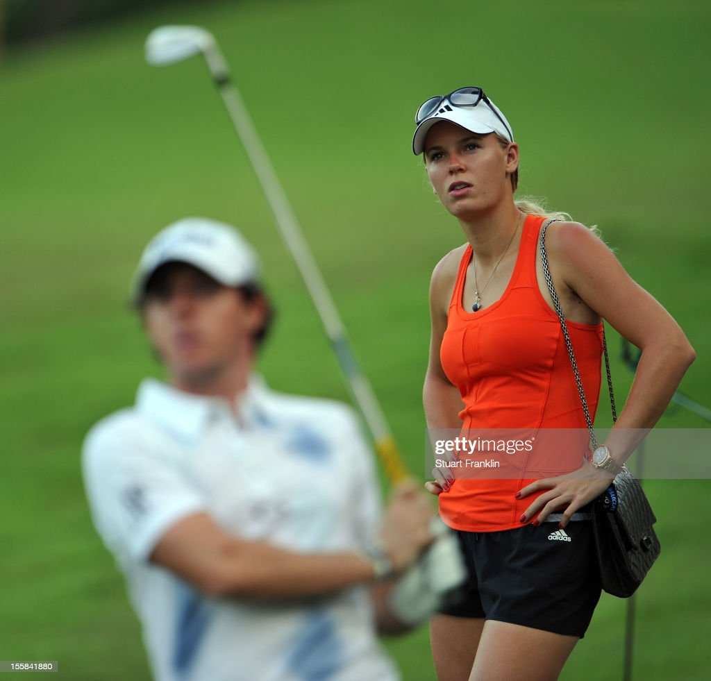 Danish tennis star, Caroline Wozniacki watches her boyfriend Rory McIlroy of Northern Ireland play a shot during the continuation of the weather delayed first round of the Barclays Singapore Open at the Sentosa Golf Club on November 9, 2012 in Singapore.