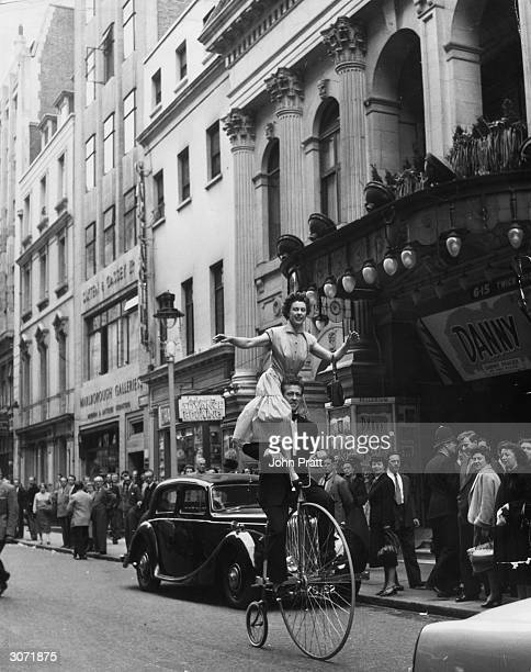 Danish trick cyclists Annell and Brask arrive at the Palladium on a pennyfarthing bicycle from their act to beat transport problems during a rail...