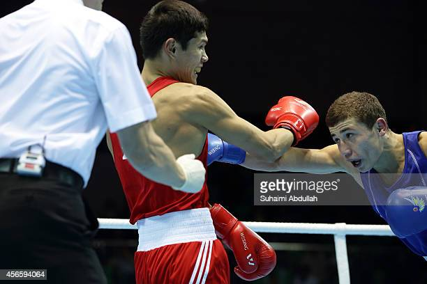 Daniyar Yeleussinov of Kazakhstan fights Israil Madrimov of Uzbekistan during the men's boxing welter weight bout final on day fourteen of the 2014...