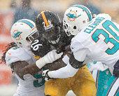 Dannell Ellerbe and Chris Clemons of the Miami Dolphins tackle Le'Veon Bell of the Pittsburgh Steelers in the first quarter at Heinz Field on...