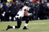 Dannell Ellerbe of the Baltimore Ravens intercepts a pass by Tom Brady of the New England Patriots in the fourth quarter during the 2013 AFC...