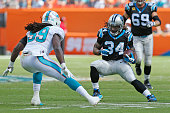 Dannell Ellerbe of the Miami Dolphins defends against DeAngelo Williams of the Carolina Panthers as he runs with the ball on November 24 2013 at Sun...