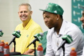 Danny Ainge listens to Marcus Smart speak to the media during a press conference on June 30 2014 at the Boston Celtics Training Center in Waltham...