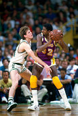Danny Ainge of the Boston Celtics guards Magic Johnson of the Los Angeles Lakers during an NBA basketball game circa 1985 at the Boston Garden in...