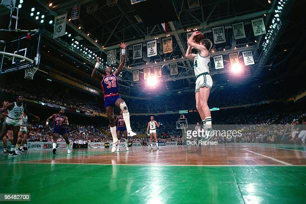 Danny Ainge of the Boston Celtics shoots a jump shot against Dan Roundfield of the Detroit Pistons during a game played in 1984 at the Boston Garden...