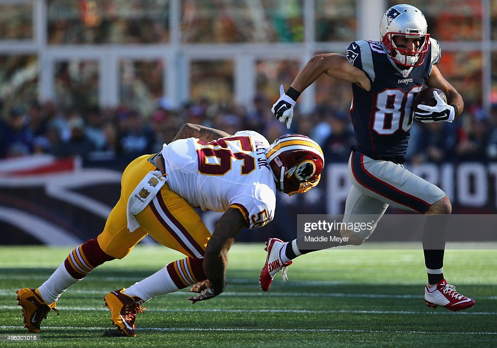 Danny Amendola of the New England Patriots carries the ball past Perry Riley of the Washington Redskins at Gillette Stadium on November 8 2015 in...