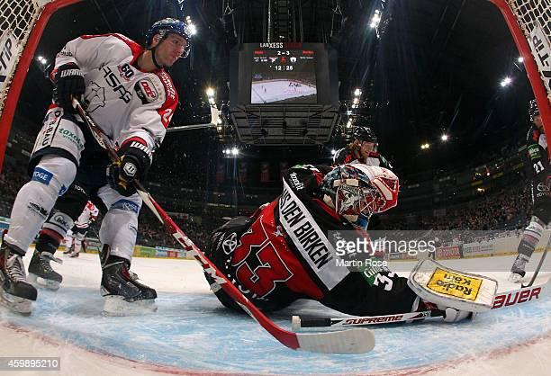 Danny aus den Birken goaltender of Koelner Haie makes a save on Darin Olver of Eisbaeren Berlin during the DEL Ice Hockey match between Koelner Haie...