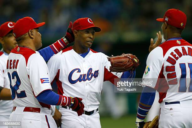 Danny Betancourt of Team Cuba is greeted by manager Victor Mesa in the dugout after the top of the sixth inning during Pool 1 Game 3 between the...
