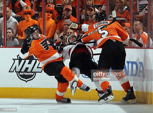 Danny Briere and Braydon Coburn of the Philadelphia Flyers combine to hit Zach Parise of the New Jersey Devils in Game Five of the Eastern Conference...