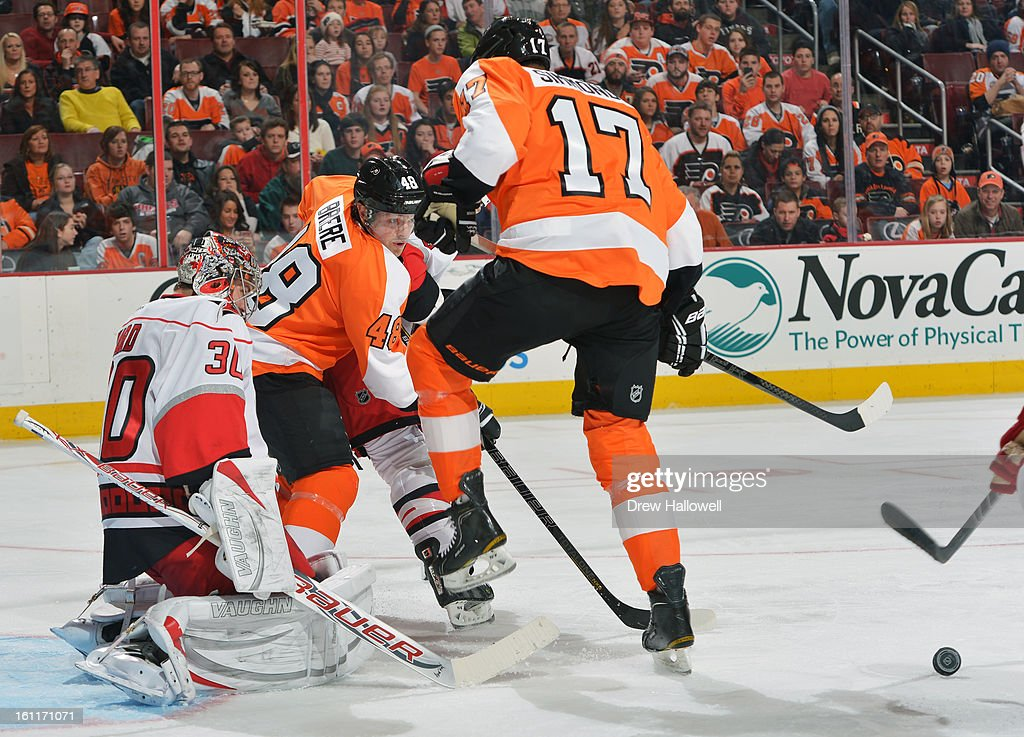 Danny Briere #48 and Wayne Simmonds #17 of the Philadelphia Flyers try to deflect the puck past Cam Ward #30 of the Carolina Hurricanes at the Wells Fargo Center on February 9, 2013 in Philadelphia, Pennsylvania.