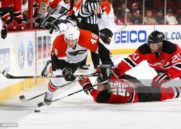 Danny Briere of the Philadelphia Flyers is tripped up by Colin White and Jay Pandolfo of the New Jersey Devils playing the puck at the Prudential...
