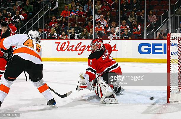 Danny Briere of the Philadelphia Flyers puts the puck past goaltender Johan Hedberg of the New Jersey Devils for a goal during the game at the...
