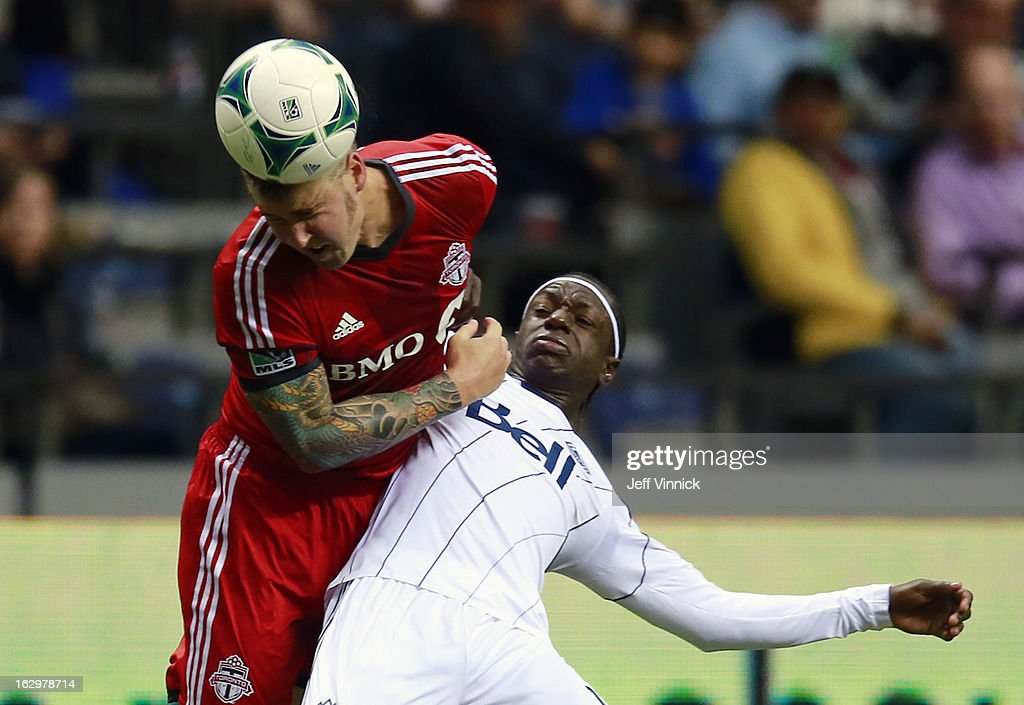 Danny Califf #3 of the Toronto FC plays the ball while fending off Darren Mattocks #11 of the Vancouver Whitecaps FC during their MLS game March 2, 2013 at B.C. Place in Vancouver, British Columbia, Canada.