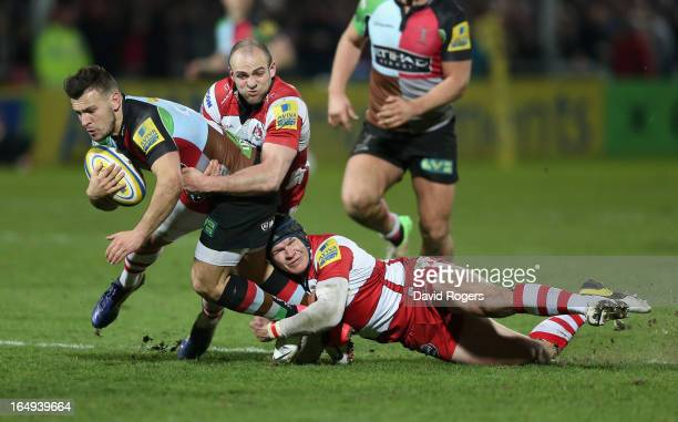 Danny Care of Harlequins is tackled by Charlie Sharples and Rob Cook during the Aviva Premiership match between Gloucester and Harlequins at...