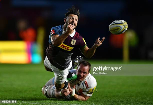 Danny Care of Harlequins offloads as he is tackled by Kai Horstmann of Exeter Chiefs during the Aviva Premiership match between Harlequins and Exeter...