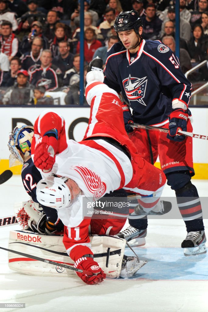 Danny Cleary #11 of the Detroit Red Wings falls over goaltender Sergei Bobrovsky #72 of the Columbus Blue Jackets in the second period as Fedor Tyutin #51 of the Columbus Blue Jackets watches on January 21, 2013 at Nationwide Arena in Columbus, Ohio.