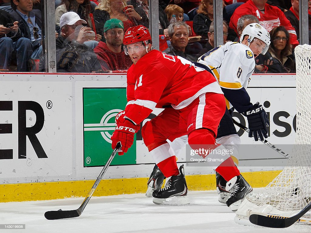 Danny Cleary #11 of the Detroit Red Wings tries to control the puck in front of Kevin Klein #8 of the Nashville Predators during the second period in Game Four of the Western Conference Quarterfinals during the 2012 NHL Stanley Cup Playoffs at Joe Louis Arena on April 17, 2012 in Detroit, Michigan.