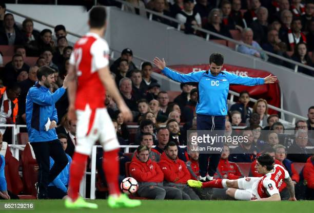 Danny Cowley manager of Lincoln City evades a sliding Hector Bellerin of Arsenal during The Emirates FA Cup QuarterFinal match between Arsenal and...
