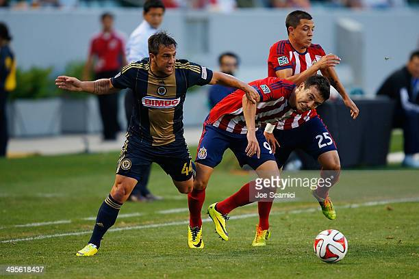 Danny Cruz of Philadelphia Union Erick Torres of Chivas USA and Donny Toia of Chivas USA fight for a ball on the sideline in the first half at...
