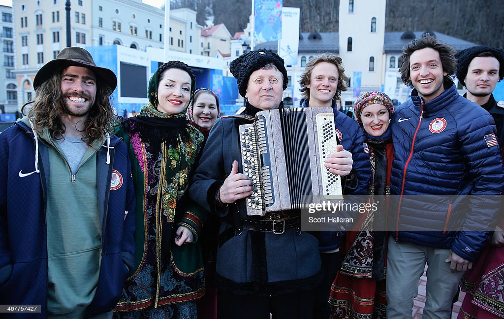Danny Davis Taylor Gold and Greg Bretz of the USA Snowboarding team pose with local residents in the Rosa Khutor Mountain Village ahead of the Sochi...