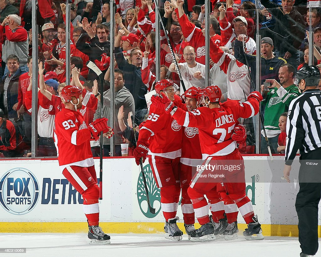 Danny DeKeyser #65, David Legwand #17, Johan Franzen #93 and Kyle Quincey #27 of the Detroit Red Wings congratulate teammate Gustav Nyquist #14 after scoring a goal during an NHL game against the Tampa Bay Lightning on March 30, 2014 at Joe Louis Arena in Detroit, Michigan. Detroit defeated Tampa Bay 3-2