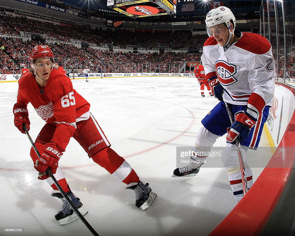 Danny DeKeyser #65 of the Detroit Red Wings and <a gi-track='captionPersonalityLinkClicked' href=/galleries/search?phrase=Alex+Galchenyuk&family=editorial&specificpeople=7419137 ng-click='$event.stopPropagation()'>Alex Galchenyuk</a> #27 of the Montreal Canadiens battle for the puck in the corner during an NHL game on March 27, 2014 at Joe Louis Arena in Detroit, Michigan.