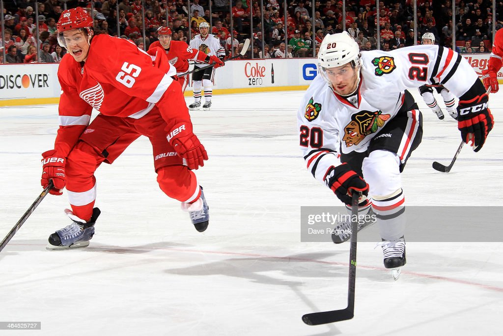 Danny DeKeyser #65 of the Detroit Red Wings and <a gi-track='captionPersonalityLinkClicked' href=/galleries/search?phrase=Brandon+Saad&family=editorial&specificpeople=7128385 ng-click='$event.stopPropagation()'>Brandon Saad</a> #20 of the Chicago Blackhawks race for the puck during an NHL game on January 22, 2014 at Joe Louis Arena in Detroit, Michigan.