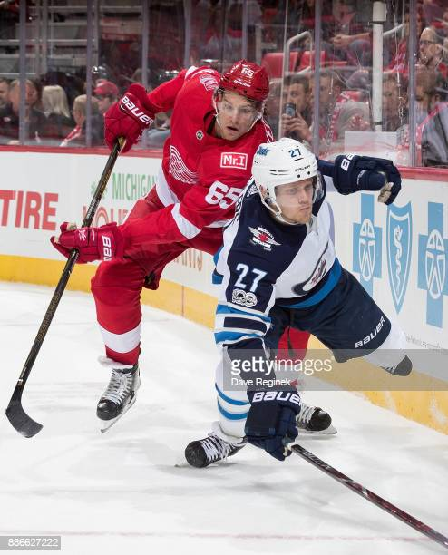 Danny DeKeyser of the Detroit Red Wings battles along the boards with Nikolaj Ehlers of the Winnipeg Jets during an NHL game at Little Caesars Arena...