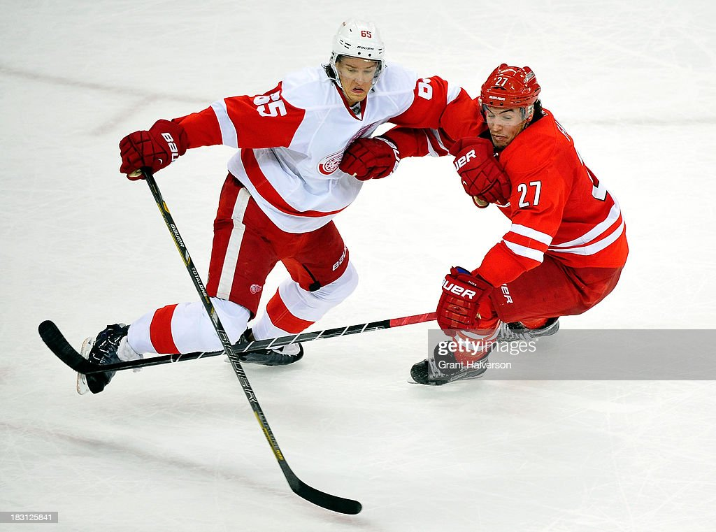 Danny DeKeyser #65 of the Detroit Red Wings battles for a loose puck with Justin Faulk #27 of the Carolina Hurricanes during play at PNC Arena on October 4, 2013 in Raleigh, North Carolina. The Red Wings defeated the Hurricanes 3-2 in overtime.