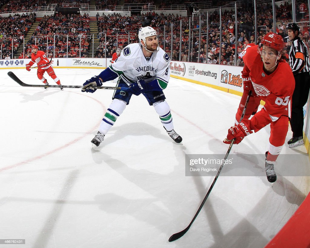 Danny DeKeyser #65 of the Detroit Red Wings clears the puck as Zack Kassian #9 of the Vancouver Canucks skates in to finish his check during an NHL game on February 3, 2014 at Joe Louis Arena in Detroit, Michigan.