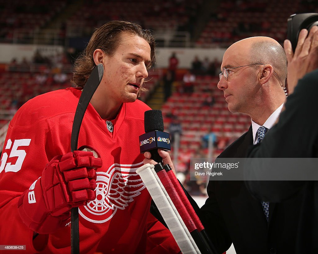 Danny DeKeyser #65 of the Detroit Red Wings does a pre-game interview with Pierre McGuire of NBCSN before an NHL game on April 2, 2014 at Joe Louis Arena in Detroit, Michigan. Detroit defeated Boston 3-2