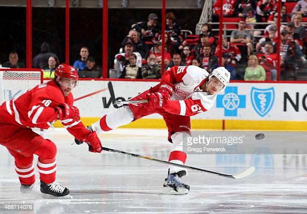 Danny DeKeyser of the Detroit Red Wings fires a puck into the zone passes the defense of Elias Lindholm of the Carolina Hurricanes during their NHL...