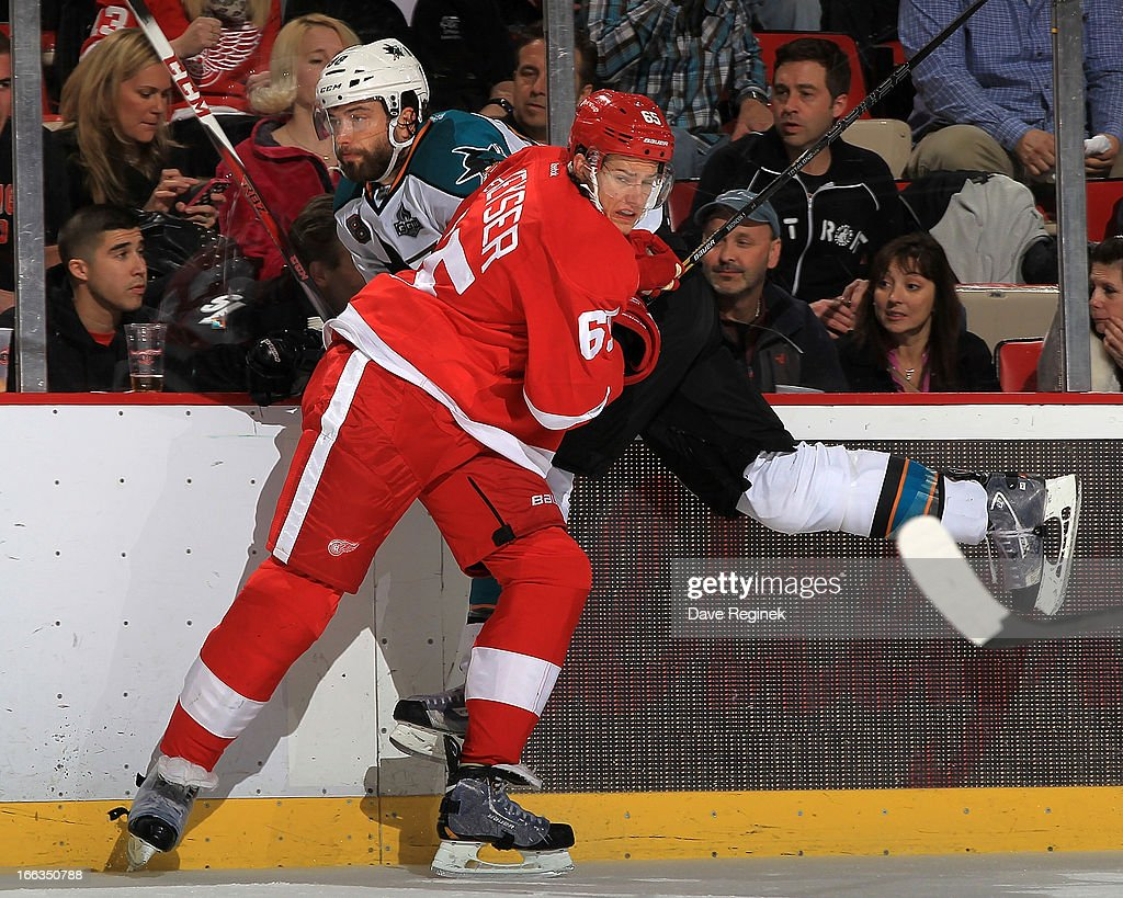 Danny Dekeyser #65 of the Detroit Red Wings hits <a gi-track='captionPersonalityLinkClicked' href=/galleries/search?phrase=Brent+Burns&family=editorial&specificpeople=212883 ng-click='$event.stopPropagation()'>Brent Burns</a> #88 of the San Jose Sharks during a NHL game at Joe Louis Arena on April 11, 2013 in Detroit, Michigan.