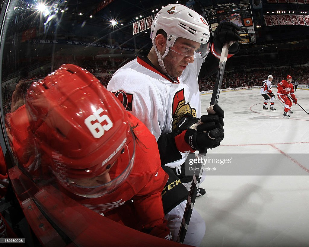 Danny DeKeyser #65 of the Detroit Red Wings is body checked into the boards by <a gi-track='captionPersonalityLinkClicked' href=/galleries/search?phrase=Eric+Gryba&family=editorial&specificpeople=570539 ng-click='$event.stopPropagation()'>Eric Gryba</a> #62 of the Ottawa Senators during an NHL game at Joe Louis Arena on October 23, 2013 in Detroit, Michigan. The Senators win 6-1
