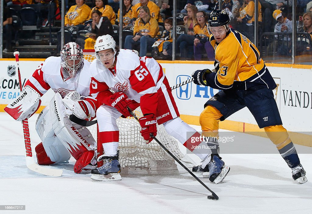 Danny DeKeyser #65 of the Detroit Red Wings looks to clear the puck against <a gi-track='captionPersonalityLinkClicked' href=/galleries/search?phrase=Nick+Spaling&family=editorial&specificpeople=4112920 ng-click='$event.stopPropagation()'>Nick Spaling</a> #13 of the Nashville Predators during an NHL game at the Bridgestone Arena on April 14, 2013 in Nashville, Tennessee.