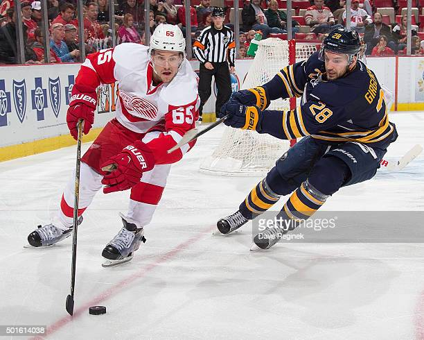 Danny DeKeyser of the Detroit Red Wings protects the puck from Zemgus Girgensons of the Buffalo Sabres during an NHL game at Joe Louis Arena on...