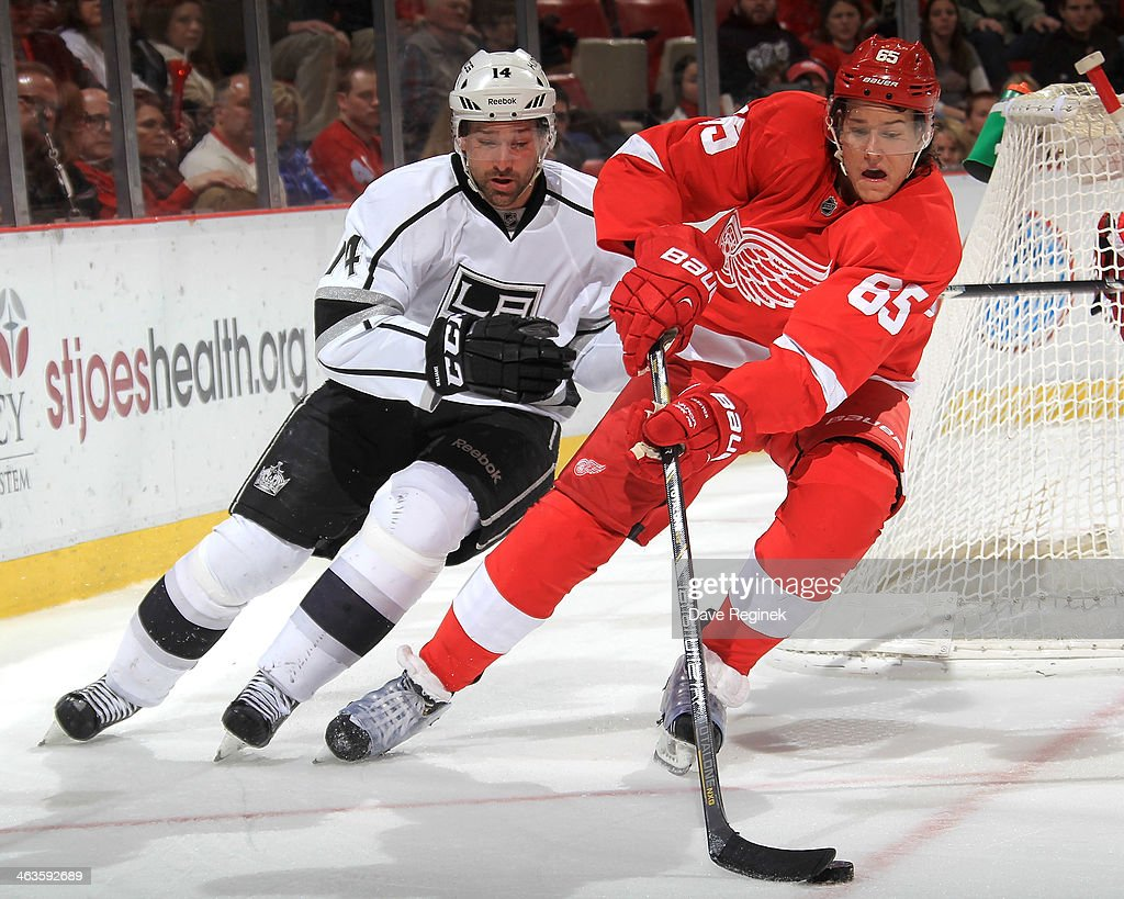 Danny DeKeyser #65 of the Detroit Red Wings skates around the net with the puck as Justin Williams #14 of the Los Angeles Kings gives chase during an NHL game on January 18, 2014 at Joe Louis Arena in Detroit, Michigan. The Red Wings defeated the Kings 3-2 in a shootout