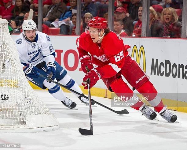 Danny DeKeyser of the Detroit Red Wings skates around the net with the puck as Nikita Kucherov of the Tampa Bay Lightning gives chase in Game Six of...