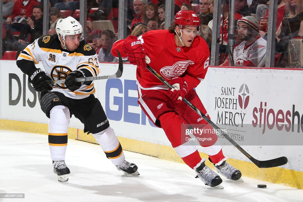 Danny DeKeyser #65 of the Detroit Red Wings skates with the puck as Brad Marchand #63 of the Boston Bruins puts a stick on him during an NHL game on April 2, 2014 at Joe Louis Arena in Detroit, Michigan.
