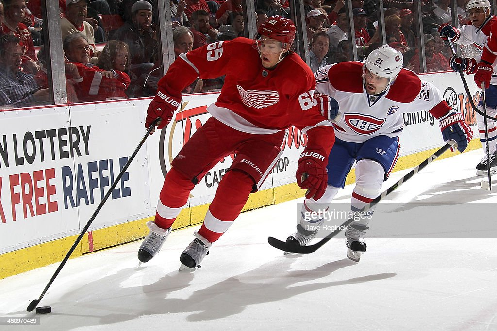 Danny DeKeyser #65 of the Detroit Red Wings skates with the puck as <a gi-track='captionPersonalityLinkClicked' href=/galleries/search?phrase=Brian+Gionta&family=editorial&specificpeople=202116 ng-click='$event.stopPropagation()'>Brian Gionta</a> #21 of the Montreal Canadiens pressures him during an NHL game on March 27, 2014 at Joe Louis Arena in Detroit, Michigan. Montreal defeated Detroit 5-4
