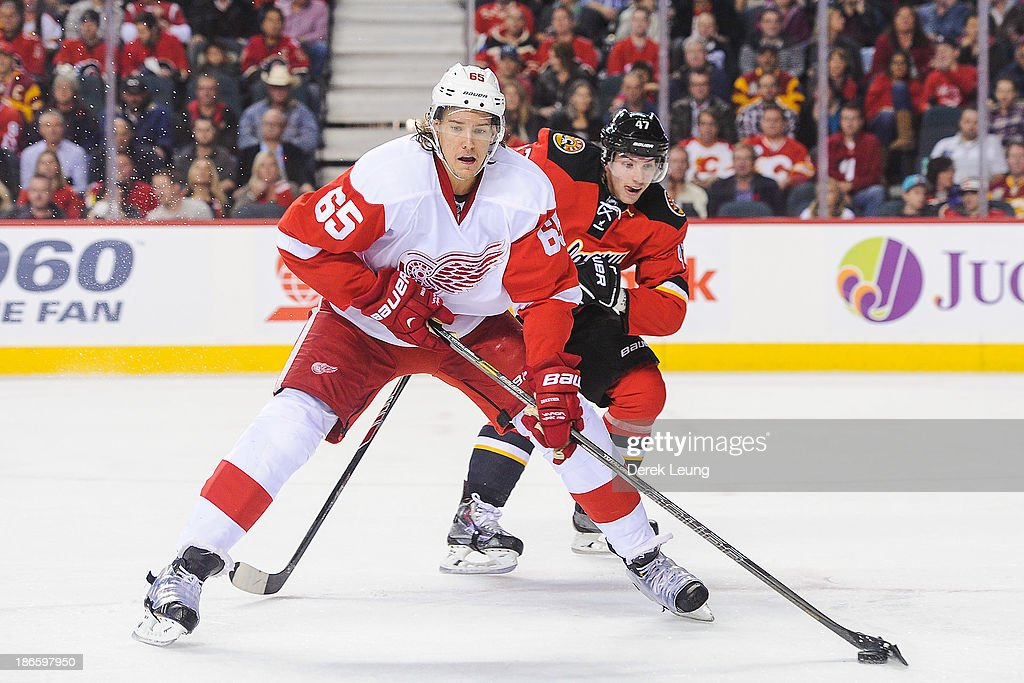 Danny DeKeyser #65 of the Detroit Red Wings skates with the puck as <a gi-track='captionPersonalityLinkClicked' href=/galleries/search?phrase=Sven+Baertschi&family=editorial&specificpeople=7832299 ng-click='$event.stopPropagation()'>Sven Baertschi</a> #47 of the Calgary Flames chases him during an NHL game at Scotiabank Saddledome on November 1, 2013 in Calgary, Alberta, Canada. The Red Wings defeated the Flames 4-3.